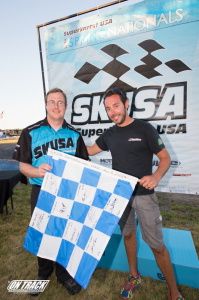 Aaron Likens handing the Saturday Autism Awareness flag to winner Mike Maurini (Photo: On Track Promotions - otp.ca)