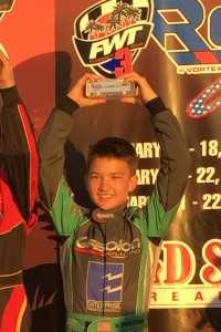 Nick Brueckner stands on the podium in the third position during his first Rok Cup USA event