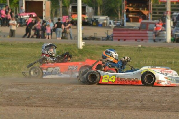 En route to his first feature win of 2015 – Junior 2 Karter Jaedon Lawson, (24) leads Donny Lampman in qualifying action (Photo: Mike Gretzinger)