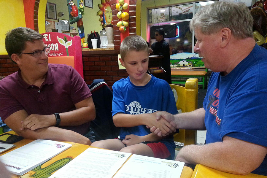 Under the watchful eyes of dad Tom Fresher (left), Jordan Fresher and Jim Howe shake on their deal for the youth to drive for Jim Howe Motorsports LLC in 2016. (Photo by Steve Driscoll)